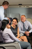 Business people passengers flying airplane talking