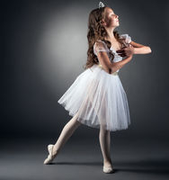 Side view of adorable little ballerina posing
