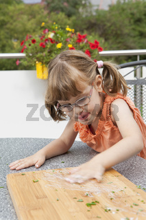 Girl blurs sauce on the cutting board