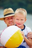 Vater und Sohn am Strand mit Wasserball