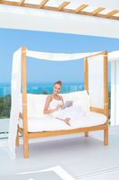 Woman sitting on a canopied day bed