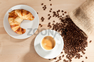 Coffee and croissant with coffee beans from the jute sack