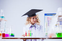 Studio shot of serious girl posing in chemical lab