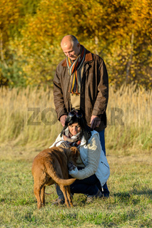 Couple playing with dog sunny autumn park