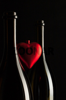 Silhouettes of elegant wine bottles with red heart