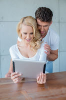 Young couple reading information on a tablet-pc