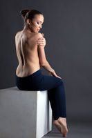 Pretty slim woman posing topless sitting on cube