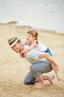 Vater trägt Tochter huckepack am Strand