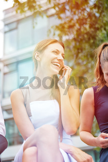 Lachende Geschäftsfrau mit Smartphone im Sommer