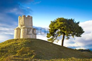 Idyllic green hill with stone church