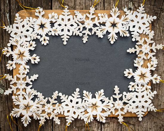 Blackboard blank framed in wooden snowflakes