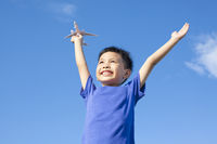 joyful little boy holding a toy with blue sky back