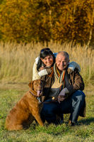Cheerful couple with dog in autumn park