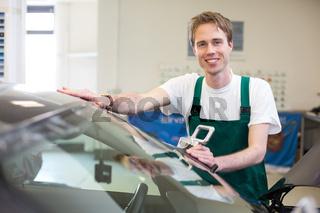 Worker in glazier's workshop installs windshield