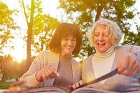 Zwei alte Frauen lesen Rezepte im Buch