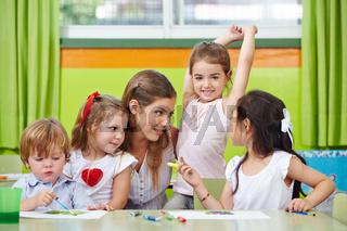 Kinder reden mit Erzieher im Kindergarten
