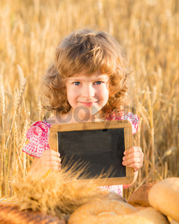 Happy child with bread in field