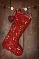 Christmas ornaments in stocking hanging on wood