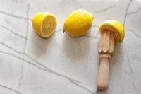 Fresh lemons and citrus reamer on marble counter t