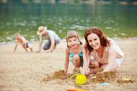 Eltern spielen mit Kindern im Sand