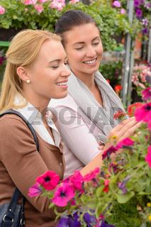 Two women choosing flowers in garden center
