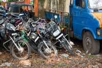 Old broken motorbikes and car in junkyard. India