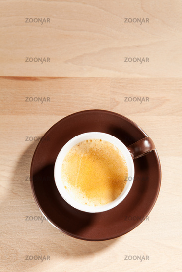 A cup of coffee standing on a wooden table