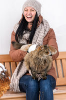 Young woman stroking cat sitting winter bench