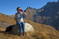 Hiker sitting on a stone and drinking from a bottl