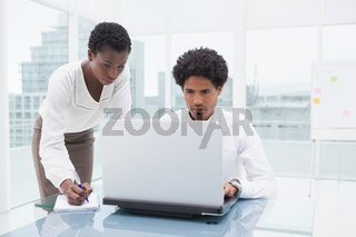 Concentrated team using laptop and taking notes