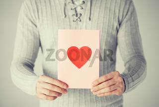 man holding postcard with heart shape