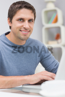 Smiling man using laptop in living room