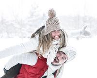 Mann trägt Frau huckepack im Winter