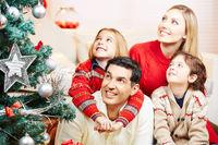 Familie und Kinder schauen Weihnachtsbaum an