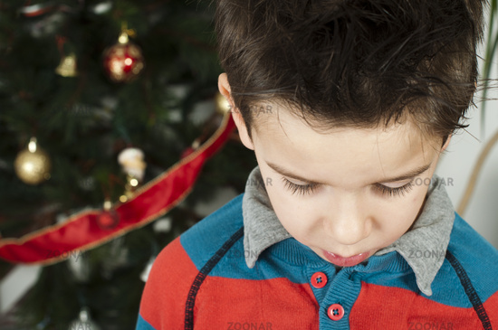 Unhappy little boy on christmass