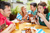 Freunde reden und flirten im Biergarten in Bayern