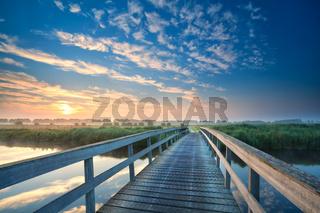 wooden bridge through the river at sunrise