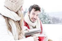 Paar trinkt Tee aus Thermoskanne im Winter
