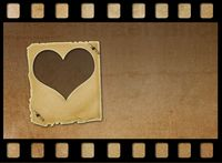 Old paper slides in the form of hearts on abstract grunge background