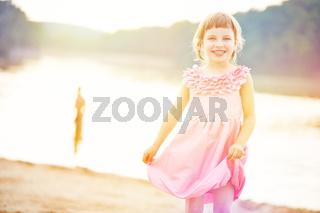 Glückliches Mädchen im Sommer am See