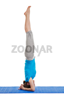 Yoga - young beautiful woman yoga instructor doing headstand (sirsasana) asana exercise isolated on white background