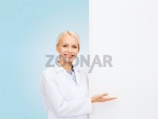 smiling female doctor with white blank board