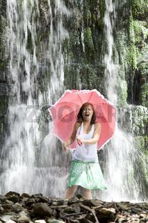 Junge Frau schreiend mit Schirm im Wasserfall