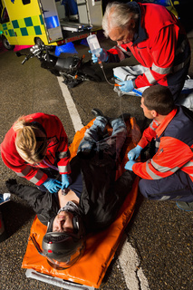 Paramedical team helping injured motorcycle driver