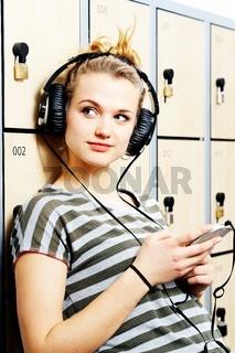 Attraktive junge blonde Studentin mit Kopfhörer