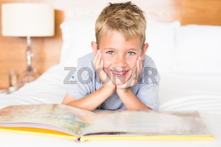 Smiling blonde boy lying on bed reading a storybook