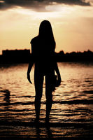 Silhouette of woman posing on the beach during sunset