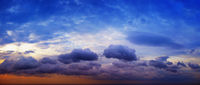 Panorama of beautiful cloudy sky with sunshine over the sea horizon