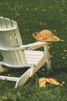 Straw hat on adirondack chair in the grass