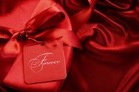 Closeup of chocolate box with gift card on satin b
